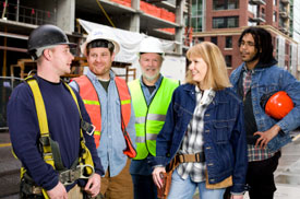 Five co-ed blue collar workers in a warehouse likely discussing the benefits of FRSACU membership.